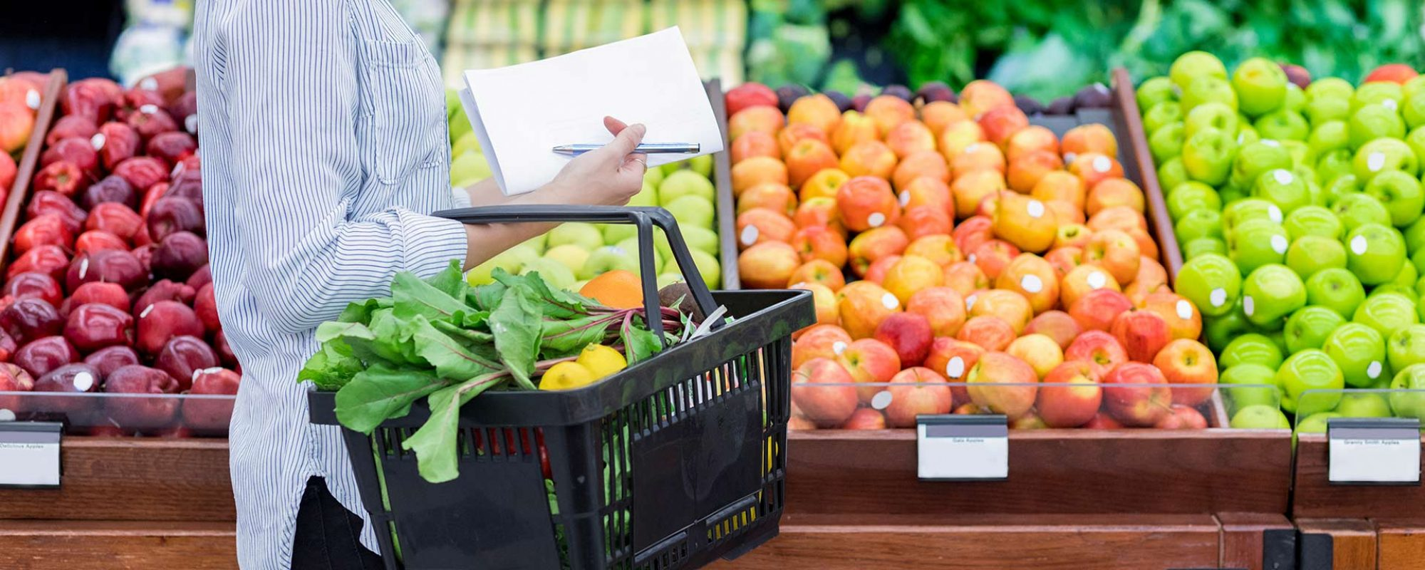 Woman with notepad picking out produce in the grocery store.